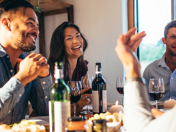 Image of friends gathering and laughing over wine and food