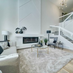 open to above great room with fireplace in the midland showhome by western living homes