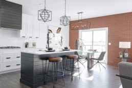 Kitchen and Dining Area with Brick Feature Wall in The Orlando Showhome in Rosewood at Secord Edmonton